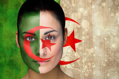 Composite image of beautiful football fan in face paint against algeria flag in grunge effect photo
