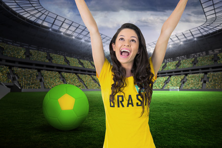 Excited football fan in brasil tshirt against large football stadium with fans in yellow photo
