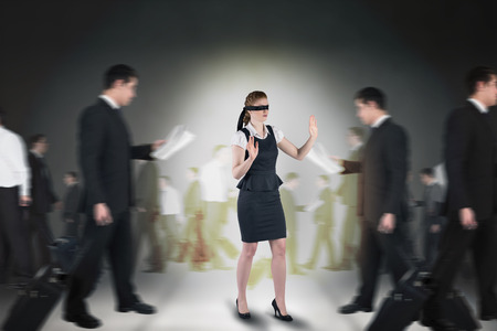 Composite image of redhead businesswoman in a blindfold against grey room photo