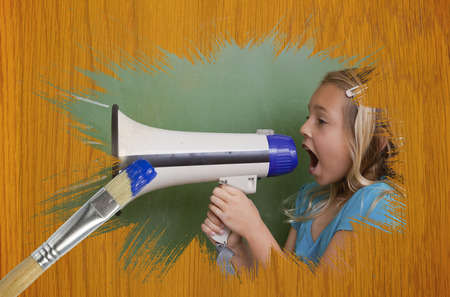 Composite image of little girl with bullhorn against wooden pine table with paintbrushes photo