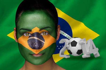 Composite image of brasil football fan in face paint against world cup 2014 with brasil flag photo