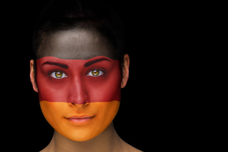 Composite image of german football fan in face paint against black photo