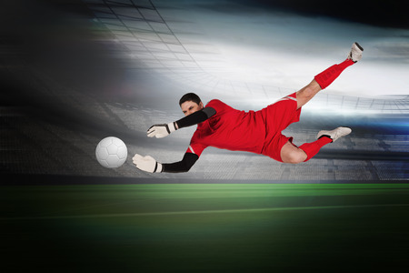 Fit goal keeper jumping up in a large football stadium with lights photo
