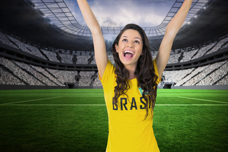 Excited football fan in brasil tshirt in a vast football stadium with fans in white photo