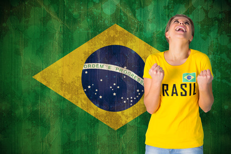 Excited football fan in brasil tshirt against brazil flag in grunge effect photo