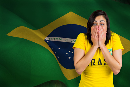 Nervous football fan in brasil tshirt against digitally generated brazil national flag photo