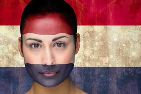 Composite image of beautiful football fan in face paint against netherlands flag in grunge effect photo