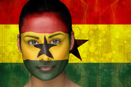 Composite image of beautiful football fan in face paint against ghana flag in grunge effect photo