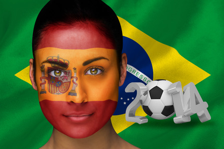 Composite image of spanish football fan in face paint against world cup 2014 with brasil flag photo