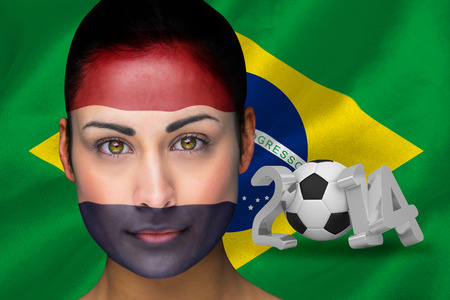 Composite image of netherlands football fan in face paint against world cup 2014 with brasil flag photo