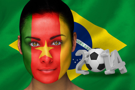 Composite image of cameroon football fan in face paint against world cup 2014 with brasil flag photo