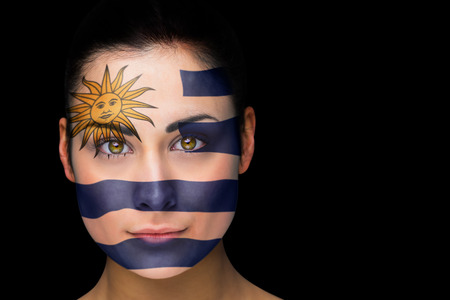 Composite image of uruguay football fan in face paint against black photo