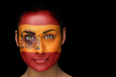 Composite image of spanish football fan in face paint against black photo