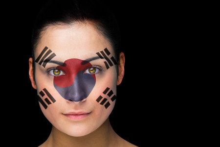 Composite image of korea football fan in face paint against black photo