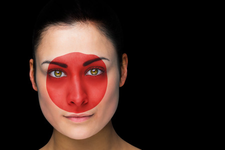 Composite image of japan football fan in face paint against black photo