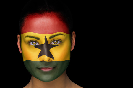 Composite image of ghana football fan in face paint against black photo