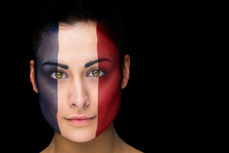 Composite image of france football fan in face paint against black photo