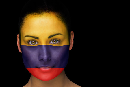 Composite image of colombia football fan in face paint against black photo