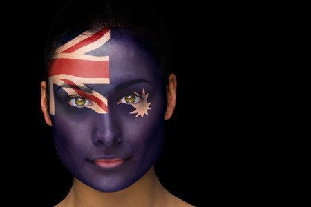Composite image of australia football fan in face paint against black photo