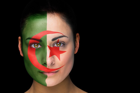 Composite image of iran football fan in face paint against black photo