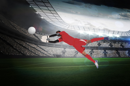 making a save: Goalkeeper in red making a save in a large football stadium with lights Stock Photo