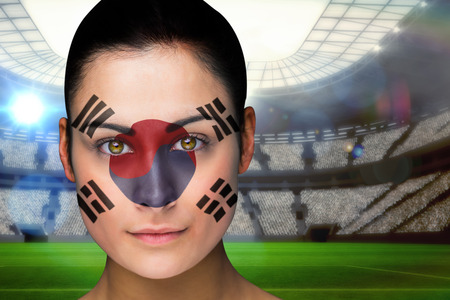 Composite image of beautiful korea fan in face paint against vast football stadium with fans in blue photo