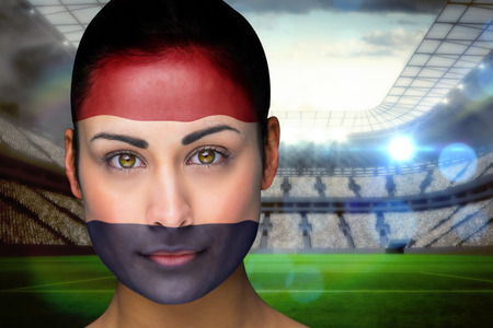 Composite image of beautiful netherlands fan in face paint against vast football stadium with fans in white photo