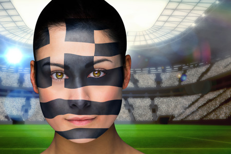 Composite image of beautiful greece fan in face paint against vast football stadium with fans in blue photo