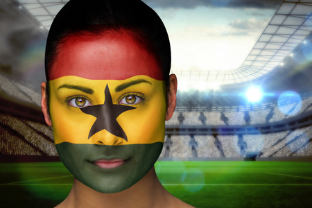 Composite image of beautiful ghana fan in face paint against vast football stadium with fans in white photo