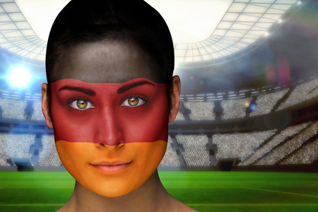 Composite image of beautiful germany fan in face paint against vast football stadium with fans in blue photo