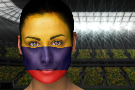 Composite image of beautiful colombia fan in face paint against vast football stadium with fans in yellow photo