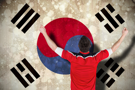 Excited football fan cheering against south korea flag photo