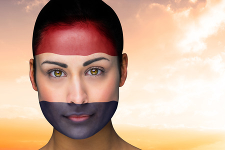 Composite image of beautiful brunette in netherlands facepaint against beautiful orange and blue sky photo