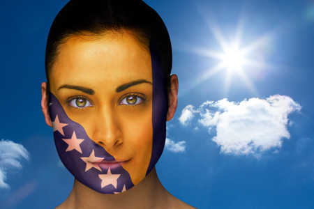 Composite image of beautiful brunette in bosnia facepaint against bright blue sky with clouds photo