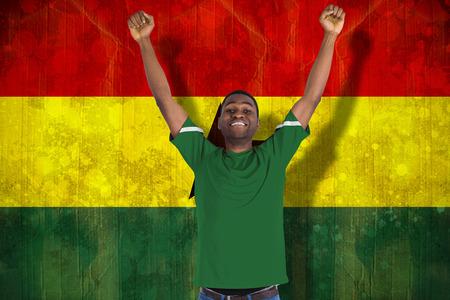 Cheering football fan in green jersey against ghana flag in grunge effect photo