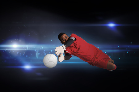 making a save: Goalkeeper in red making a save against black background with spark