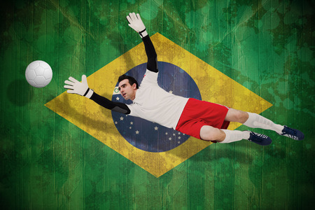 making a save: Goalkeeper in white making a save against brazil flag in grunge effect Stock Photo