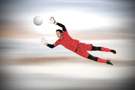 goal keeper: Fit goal keeper jumping up against grey blurred background Stock Photo