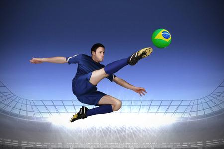 Football player in blue kicking against large football stadium with spotlights under dark blue sky photo