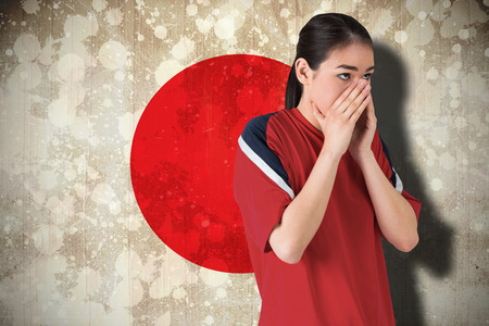 Composite image of nervous football fan looking ahead against japan flag photo