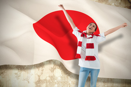 Composite image of excited asian football fan cheering against japan flag photo