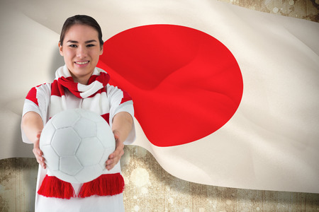 Composite image of football fan in white wearing scarf holding ball against japan flag photo