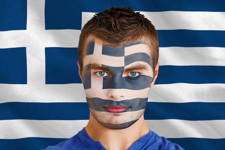 Composite image of serious young greece fan with facepaint against digitally generated greek national flag photo