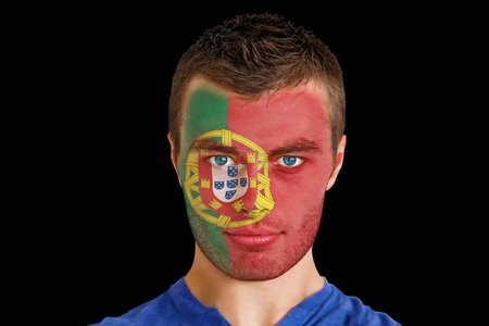 Composite image of serious young portugal fan with facepaint against black photo