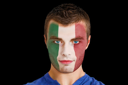 Composite image of serious young italy fan with facepaint against black photo