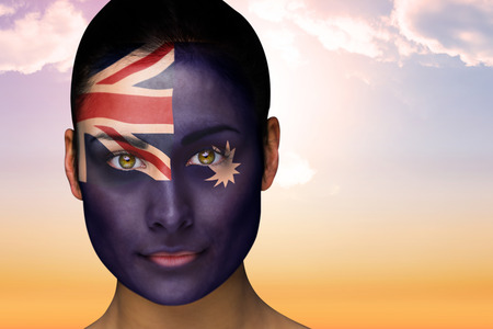 Composite image of beautiful brunette in australia facepaint against beautiful orange and blue sky photo