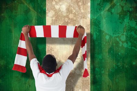 Happy football fan waving scarf against nigeria flag in grunge effect photo