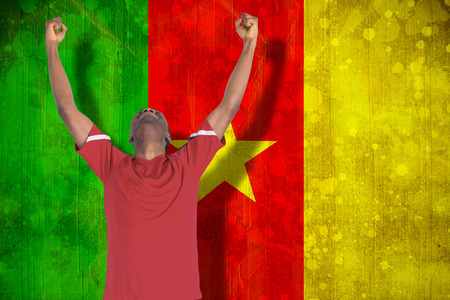 Excited handsome football fan cheering against cameroon flag in grunge effect photo