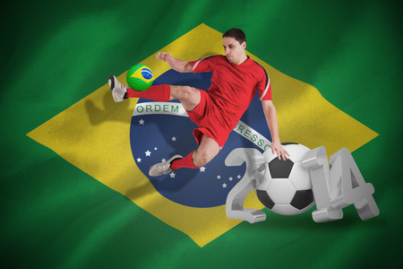 Fit football player jumping and kicking against world cup 2014 with brasil flag photo