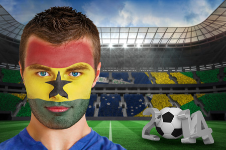 Composite image of serious young ghana fan with face paint against large football stadium photo
